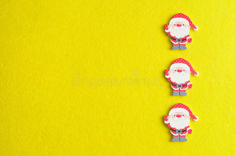 Row of Santa clauses. On a yellow background stock photos