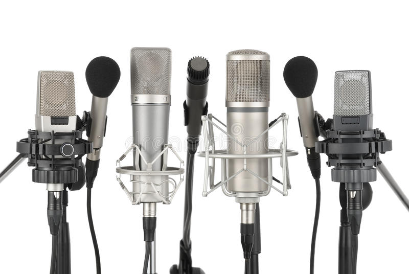 Row of seven microphones. Studio shot of seven professional microphones in a row on white background royalty free stock photo