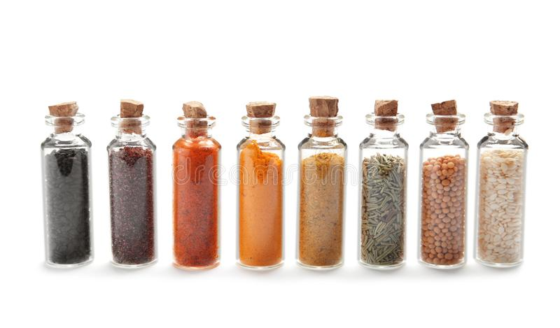 Row of small glass bottles with different spices. On white background stock photos