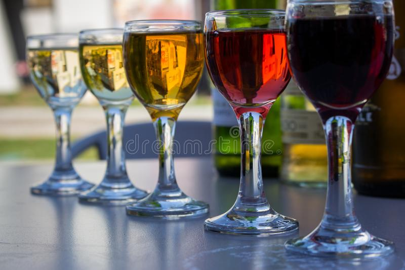 Row of small wine glasses with different wine. Glasses with white, rose and red wine. Wine set. Alcohol drinks concept royalty free stock image
