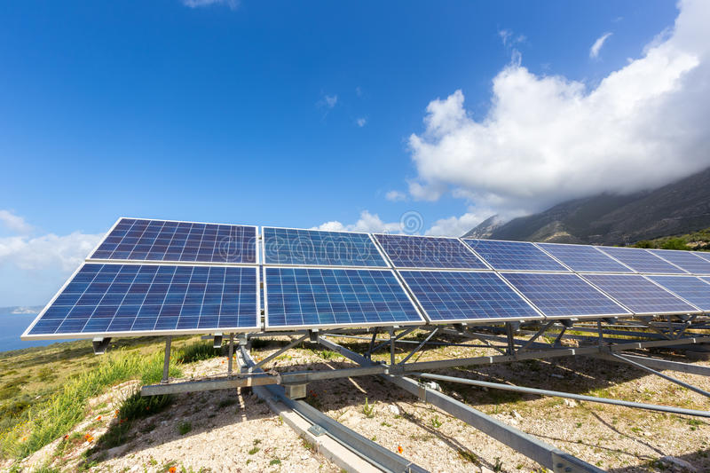 Row of solar collectors on mountain with blue sky. Row of solar collectors or solar panels on mountain with blue sky and white clouds stock photography