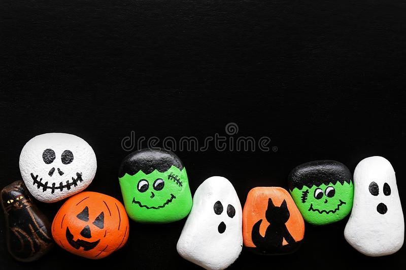 Row of Spooky Cartoon Halloween Painted Rocks Lined up Along Bot royalty free stock image