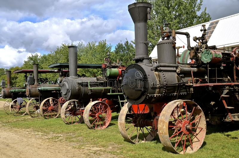 Row of steam engines. Old steel wheeled steam engines are lined up in a row royalty free stock image
