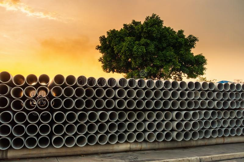 Row of Storage Sewage Drainage Concrete Pipeline, Manufacturing Plant of Material Construction, Stack of Culvert Pipe and Water stock image