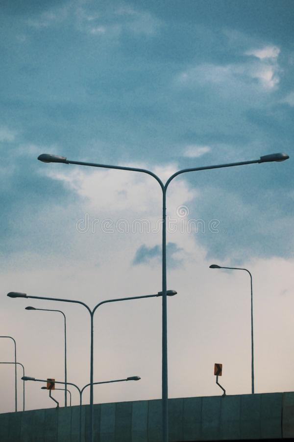 A row of street lights/lamps silhouetted against a blue sky. LED road lighting. Road lighting poles. A lot of road lanterns royalty free stock image