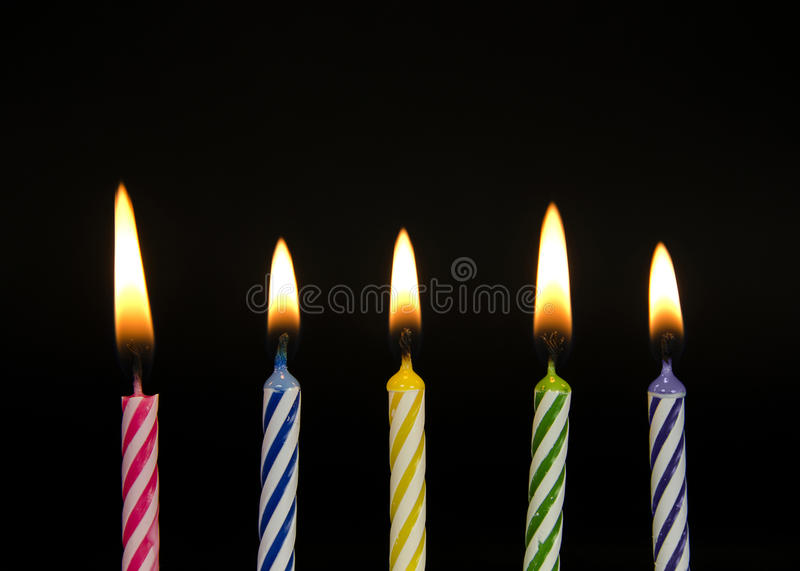 Row of striped birthday candles. Row of glowing striped birthday candles on a black background royalty free stock photo