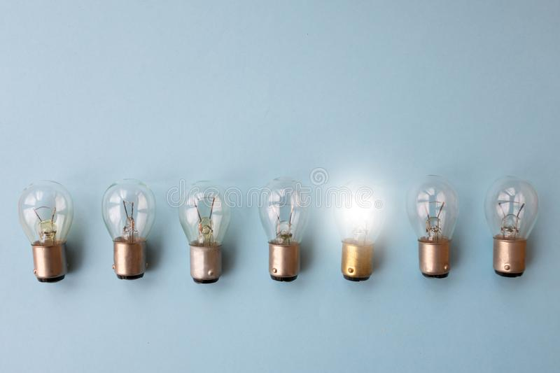 Row of switched off light bulbs with one switched on. Concept of having idea and creativity royalty free stock photo