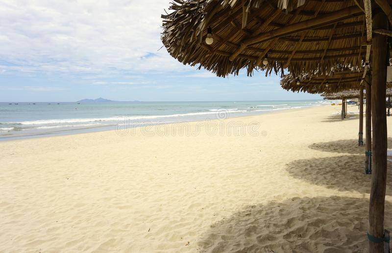Thatched roof sunshades on a sandy beach with surf and blue sky in Vietnam. A row of thatched roof sun shelters offer a view of the tropical sandy beach royalty free stock photography