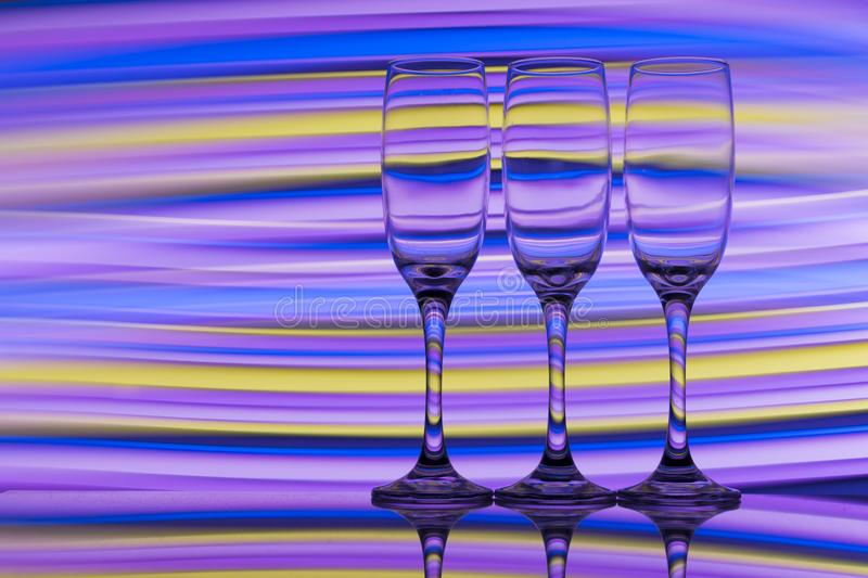 Three champagne glasses in a row with a rainbow of colorful light painting behind them stock image