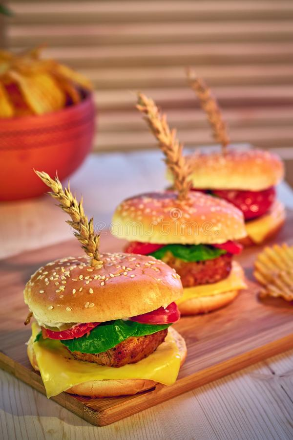 Row of three fashionable mouth-watering hamburgers on wooden board in restaurant. Selective focus, perspective. Tempting fast food stock photo