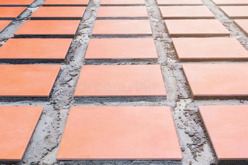 Row tile ceramic orange on floor install with cement in work construction renovation outdoor home royalty free stock photos