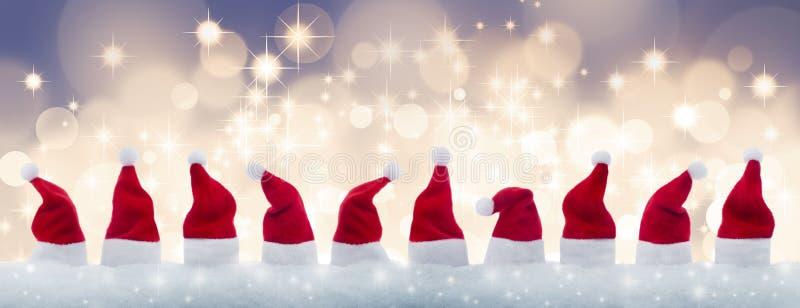 Row of tiny Santa Claus hats in the snow stock illustration