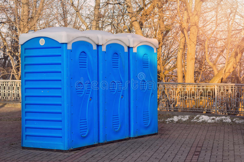 Row of toilets. A row of bio toilets in public place hit by the sun stock image