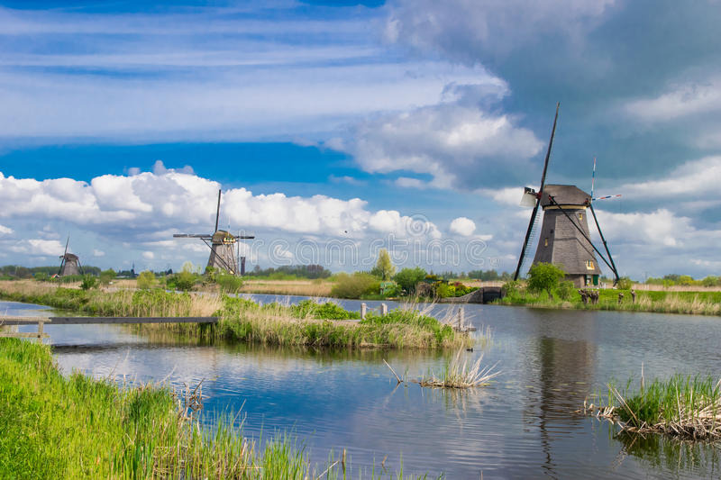 Row of traditional wind mills along blue canal in Kinderdijk, Holland. Traditional wind mills along blue canal in Kinderdijk, Holland stock photography