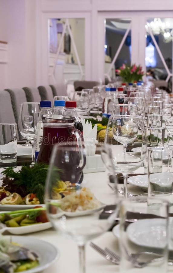 A row of transparent empty glasses and plates with snacks stock photo