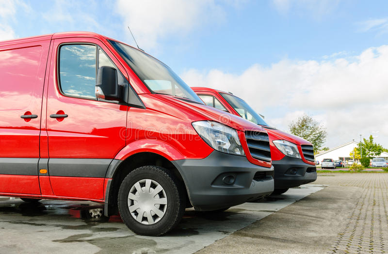 Row of two red delivery and service vans in front of factory delivery parcel hub center royalty free stock photo