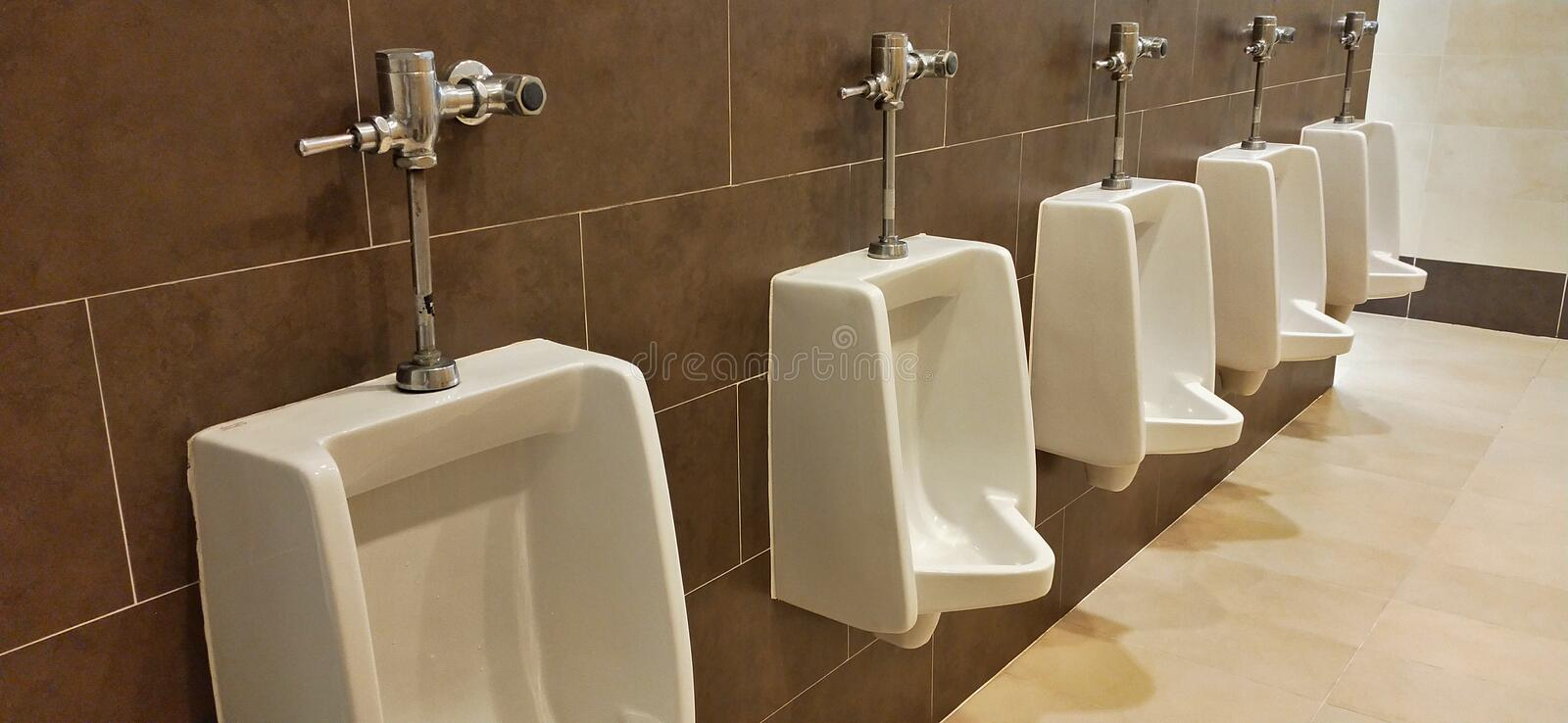 Row of Urinal with brown wall in male restroom royalty free stock photography