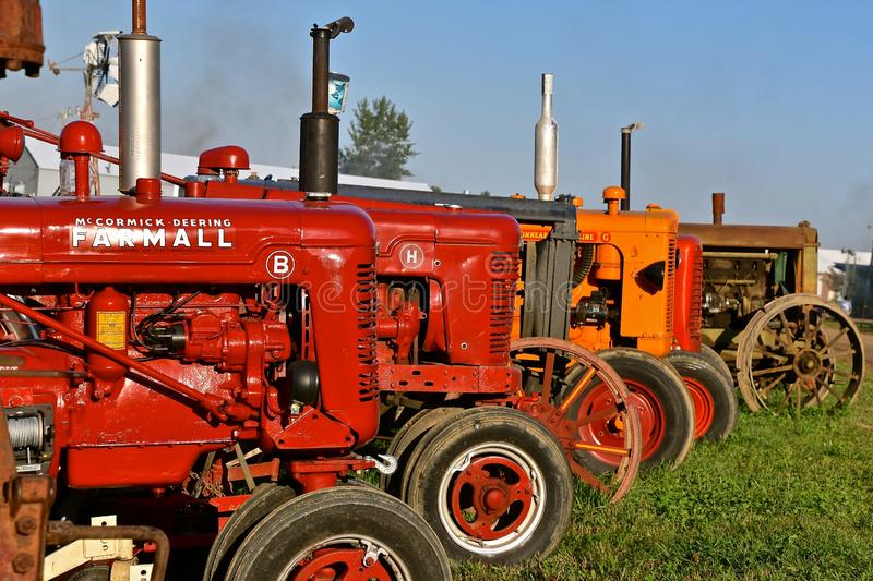 Row of various colored old tractors. ROLLAG, MINNESOTA, September 1, 2018: A row of old tractors features Farmall M and B`s are on display at the annual WCSTR royalty free stock photography