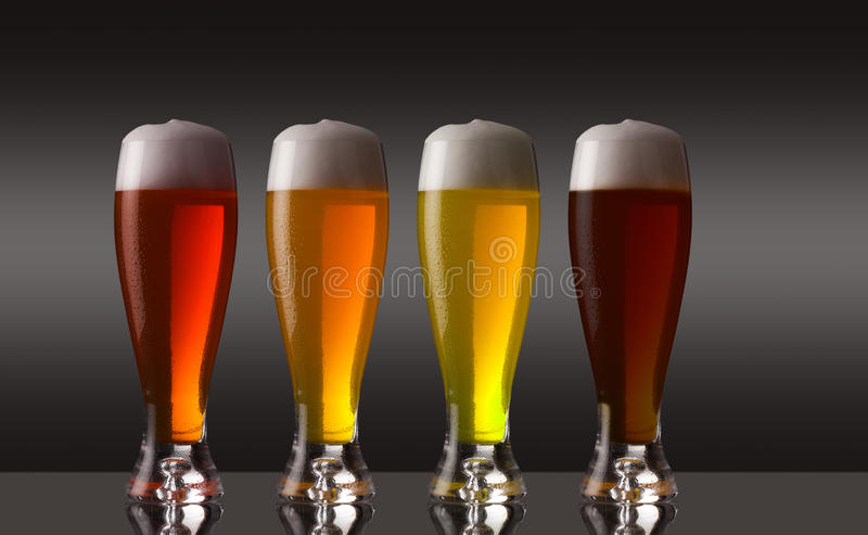 Row of various types of beer with foam stock photo