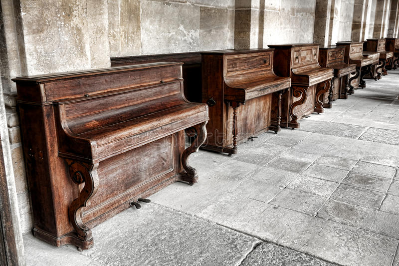 Row of Vintage Upright Piano in Old Music School. Row of vintage upright study pianos with weathered wood cabinet in an old music school lesson hall with antique stock photo