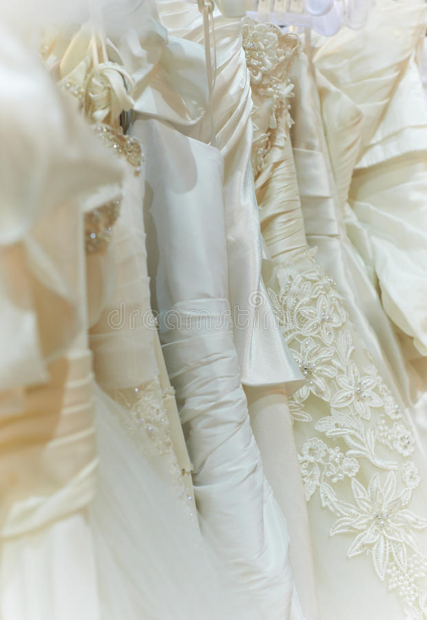 Row of wedding clothes. Smooth white satin wedding dresses in a row with different shiny style, folds, creases royalty free stock photography