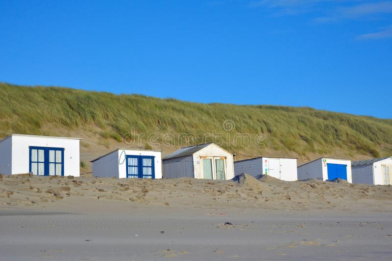 Row of white and blue beach sheds on the beach of island Texel in the Netherlands stock image