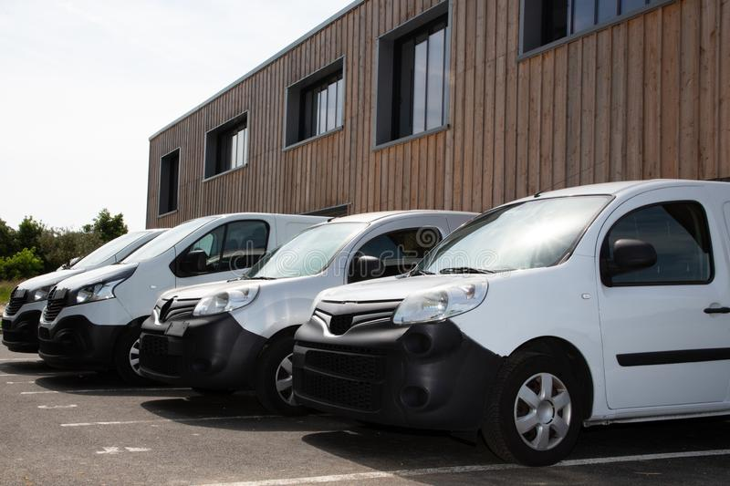 Row white delivery service van small trucks park front of factory warehouse distribution plant. A Row white delivery service van small trucks park front of stock image