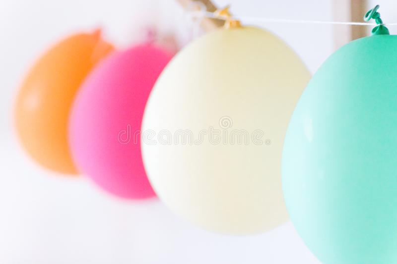 Row of white pink orange turquoise air balloons hanging in kids room. Birthday party baby shower decoration celebration fun stock images
