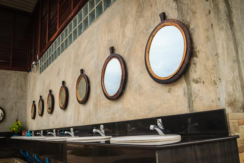 Row of white wash basins in the bathroom with row of mirrors in. A public toilet. White clean ceramic sink bowls in the public men's toilet stock photos
