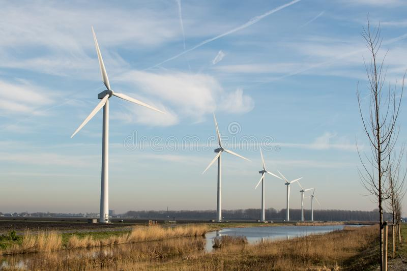 A row of windmills at the side of a waterway in the Netherlands near Alkmaar stock photo
