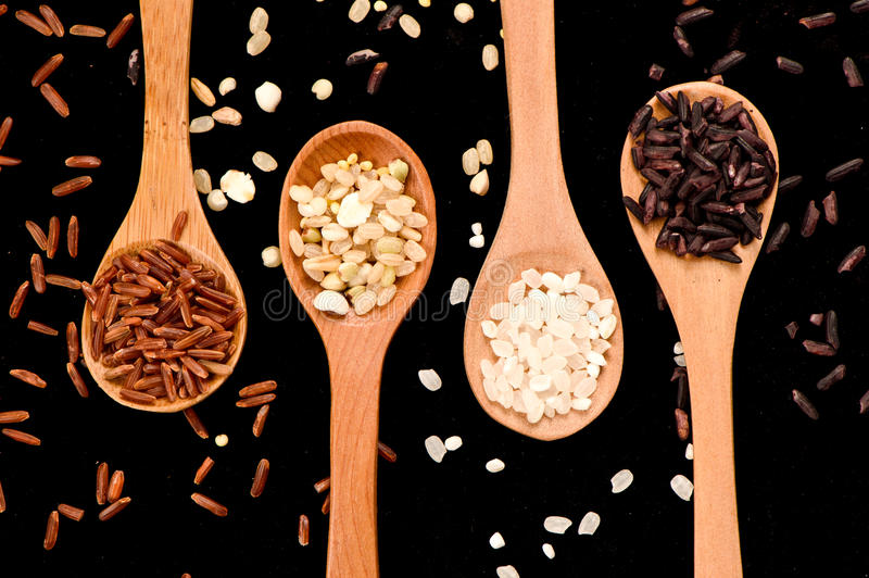 Row of wood spoons with various rice:white rice,blck rice, red rice and grain rice royalty free stock photos
