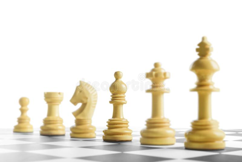 Row of wooden chess piece. On the chessboard stock photography