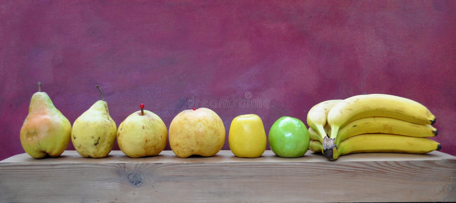 Row of yellow fruits and one green apple royalty free stock image