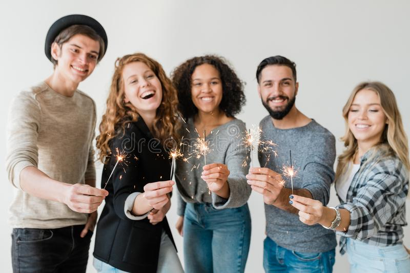 Row of young excited friends holding sparkling bengal lights in front of camera stock photography