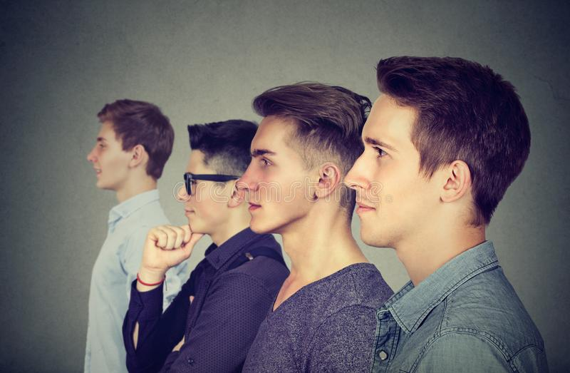 Row of young men posing on gray. E view of four young men standing in row and looking forward on gray backdrop royalty free stock photo