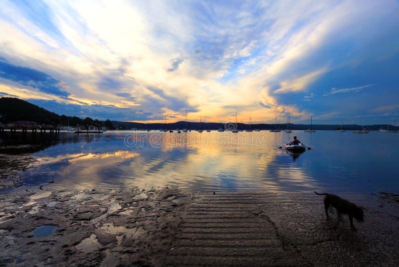 Rowboat приходя подпирать в заходе солнца позднего вечера стоковое изображение
