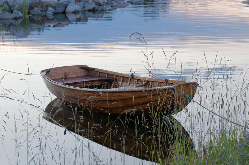 Rowboat in calm water in the harbour. Wooden rowboat in the calm water in a small harbor in the evening light. Front side view. Grass in the foreground royalty free stock images