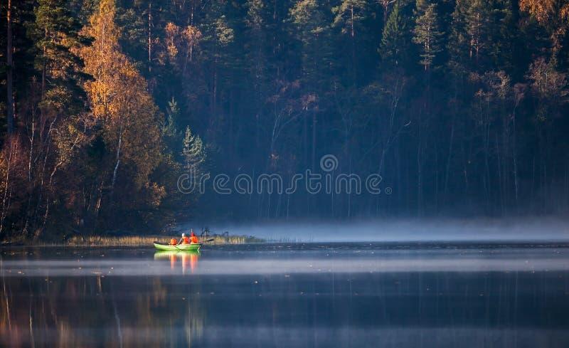 Rowboat con la gente sul lago selvaggio fotografia stock