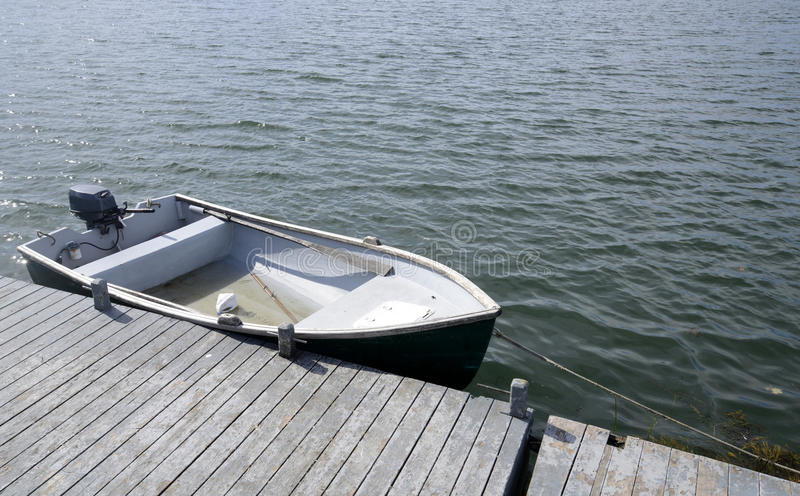 Rowboat by a wood pier royalty free stock photo