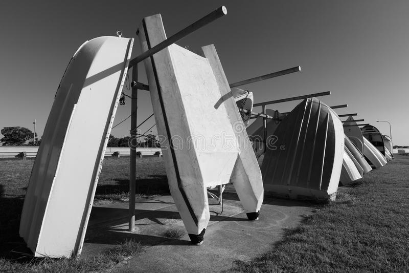 Rowboats/λέμβοι, που παρατάσσεται σε ένα ράφι βαρκών μαύρο λευκό στοκ φωτογραφία
