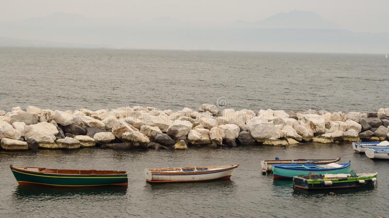 RowBoats in the harbour in Naples Italy. Sotone, stone, coast, sea, ocean, mediterranean, fishing, port, rock, travel, vessel, sailing, europe, tourist, color royalty free stock image