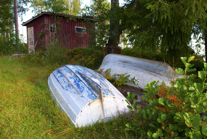 Rowboats in front of red shed royalty free stock photos