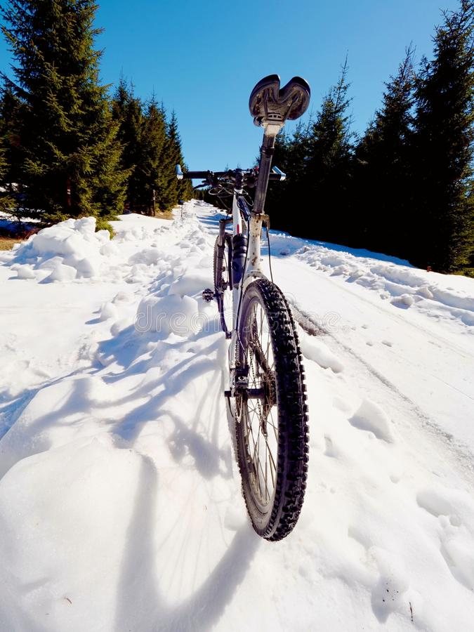 Rower górski pozycja w zamarzniętym śniegu przeciw niebieskiemu niebu Chowana asfaltowa droga zdjęcie royalty free