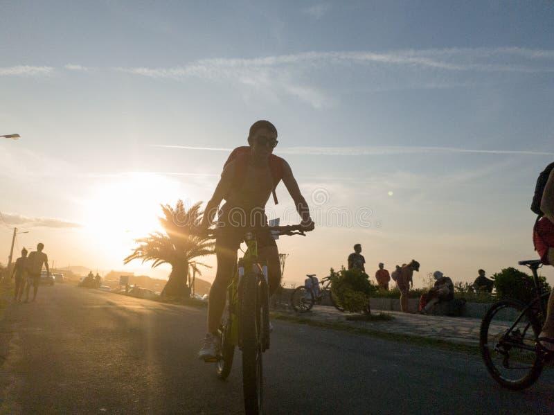 Rower i ludzie na zachodzie słońca na plaży zdjęcia stock