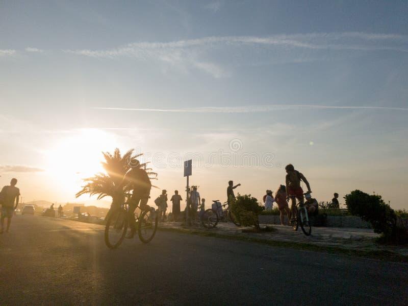 Rower i ludzie na zachodzie słońca na plaży zdjęcie royalty free