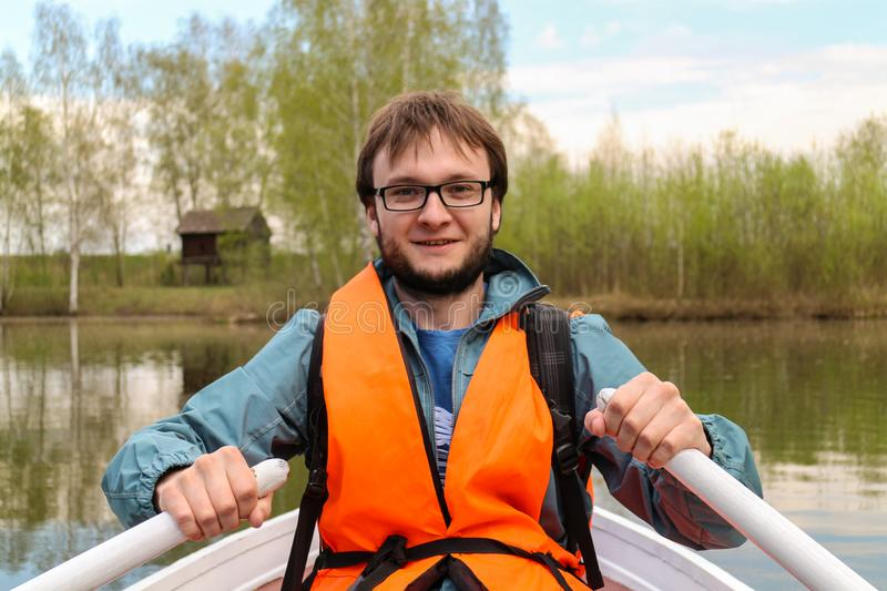 Rower man in the lifejacket in the boat royalty free stock image
