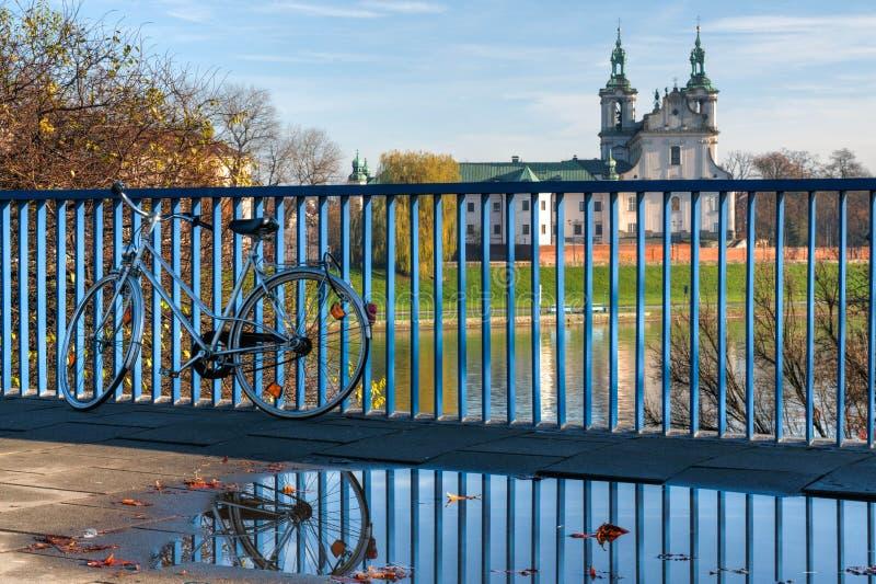 Rower pozycja blisko do kałuży na Krakow moście z odbiciem obrazy stock