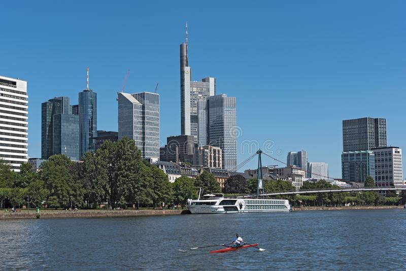 Rower in red boat on the main river in front of the skyline, frankfurt, germany stock image