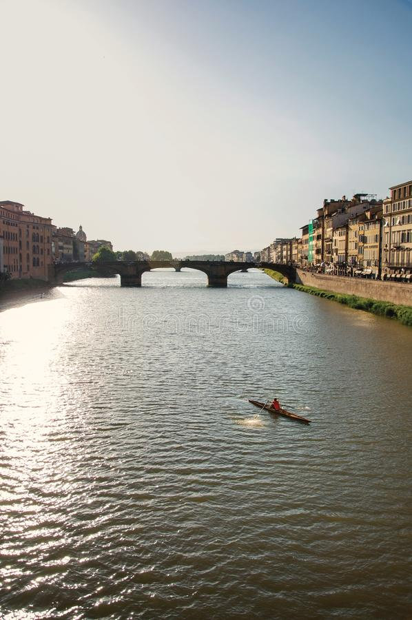 Rower on the river Arno with bridge at sunset in Florence stock images