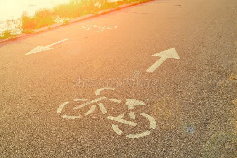 Rowerowi drogowi znaki drukujący na asfalcie z pointerem pokazuje sposób zdjęcia royalty free